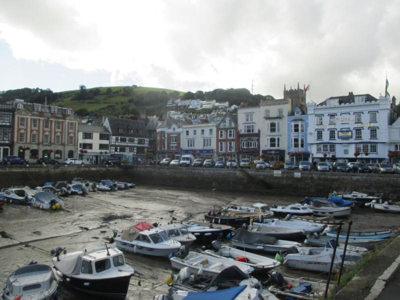 Dartmouth's little boat harbour, low tide, surrounded by shopping streets, pubs, and cafes.
